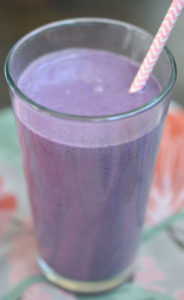 Tell peanut butter and jelly smoothie over flowery tapestry.