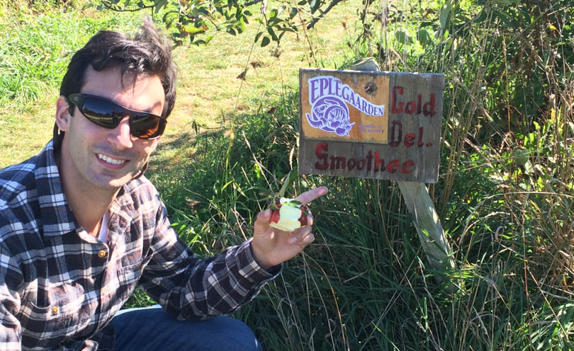 Lenny Gale in front of sign at apple orchard saying smoothie sign