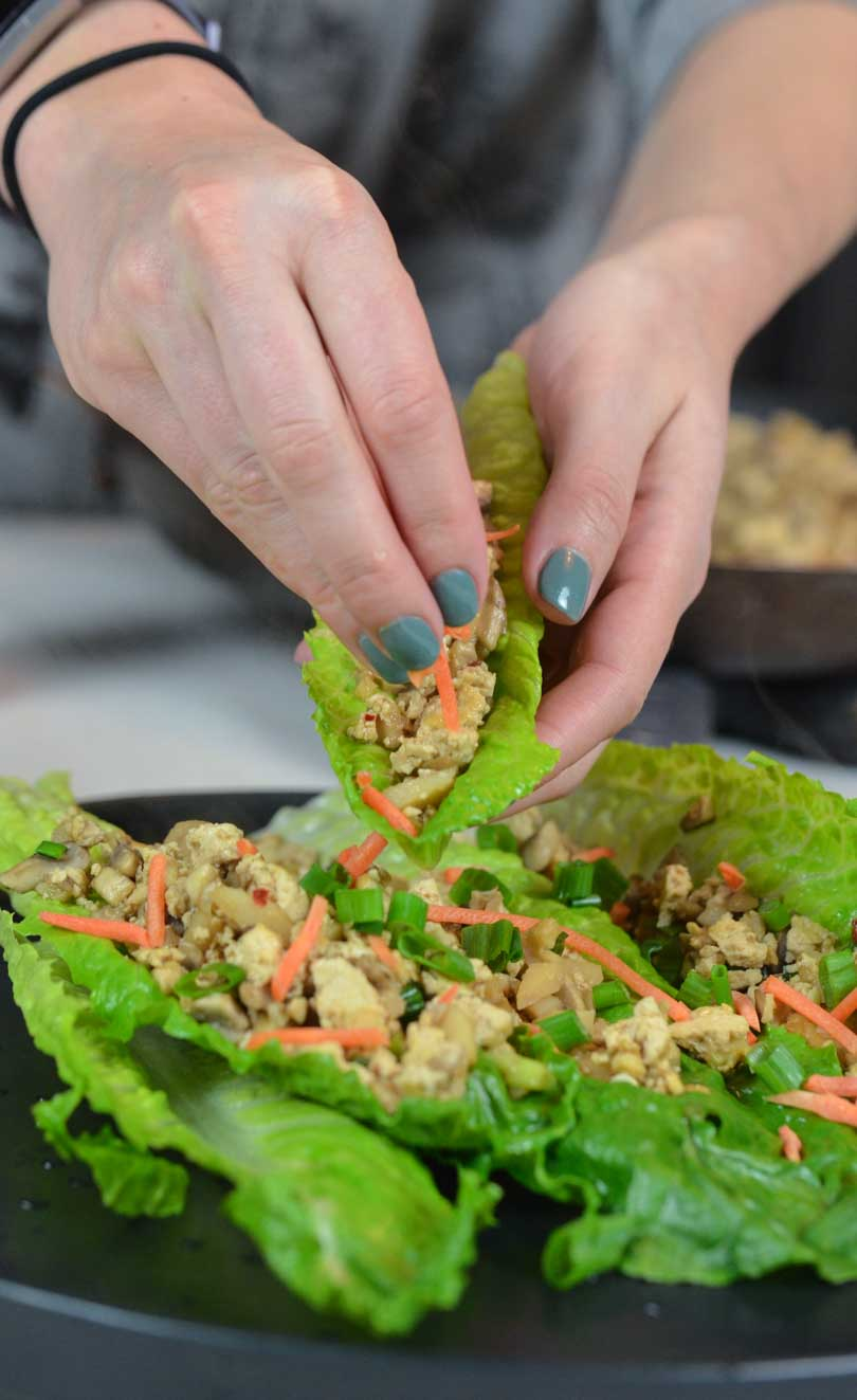 Asian lettuce wraps being assembled by pretty woman hands.