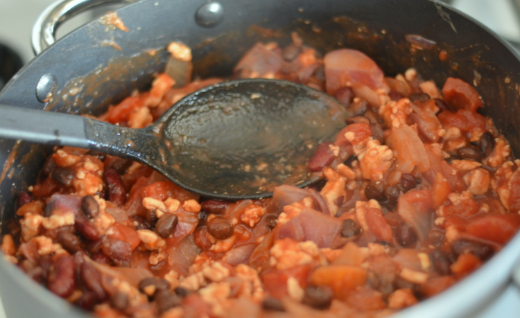 Serving spoon in big pot of five alarm chili