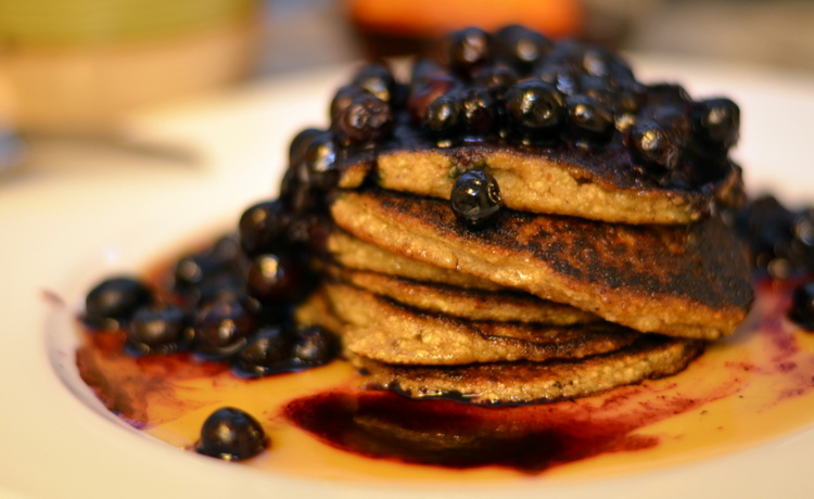 Matzah pankcakes covered in maple syrup and hot blueberries on white plate with coffee in background