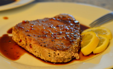 Ahi Tuna Served on white plate with soy sauce and lemon wedge
