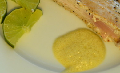 Garlic Lime Aioli on corner of white plate served with albacore tuna garnished with lime