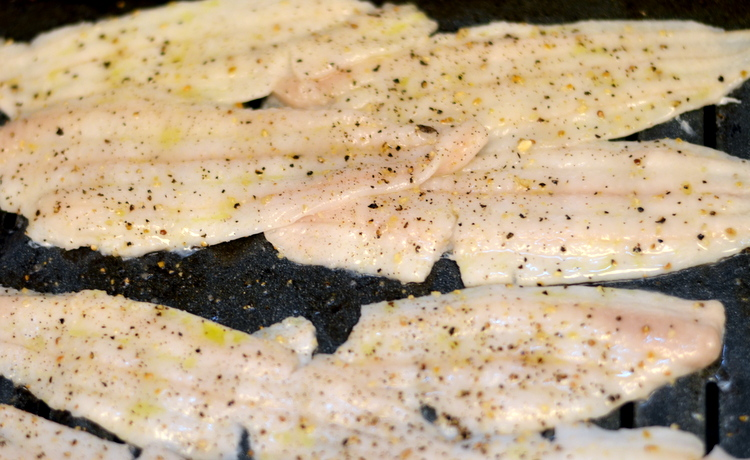 Uncooked Dover Sole Fillets on broiler pan with salt pepper ready to be cooked