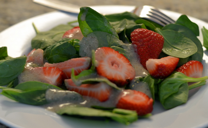 white bowl with fork on side filled with spinach strawberry salad and chia seed dressing