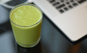 Green smoothie next to my laptop for Vitamix vs Blendtec
