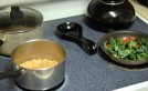 Making quinoa, beans and kale tomato mix for quinoa burrito bowl.
