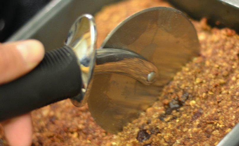Using pizza slicer to cut homemade granola bars