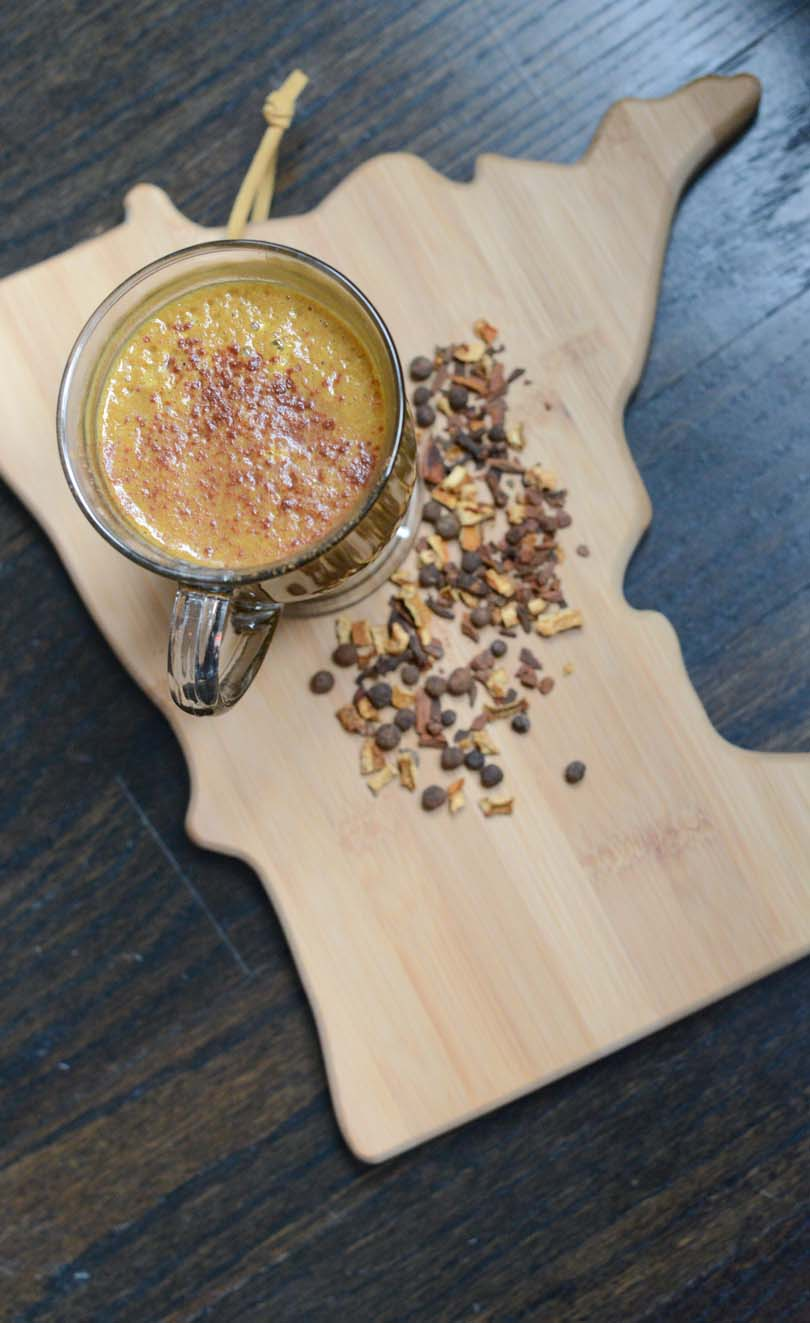 Pumpkin spice latte on Minnesota cutting board with seasoning sprinkled around.