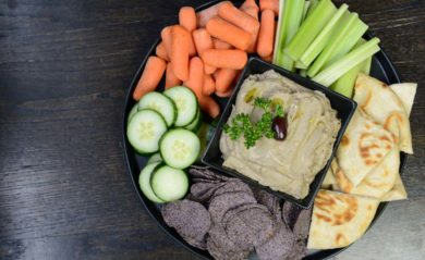 Black olive hummus served with vegetables, pita, and chips.