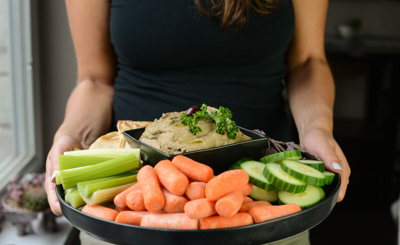 Black olive hummus served on a platter with veggies and pita and chips by Shalva.