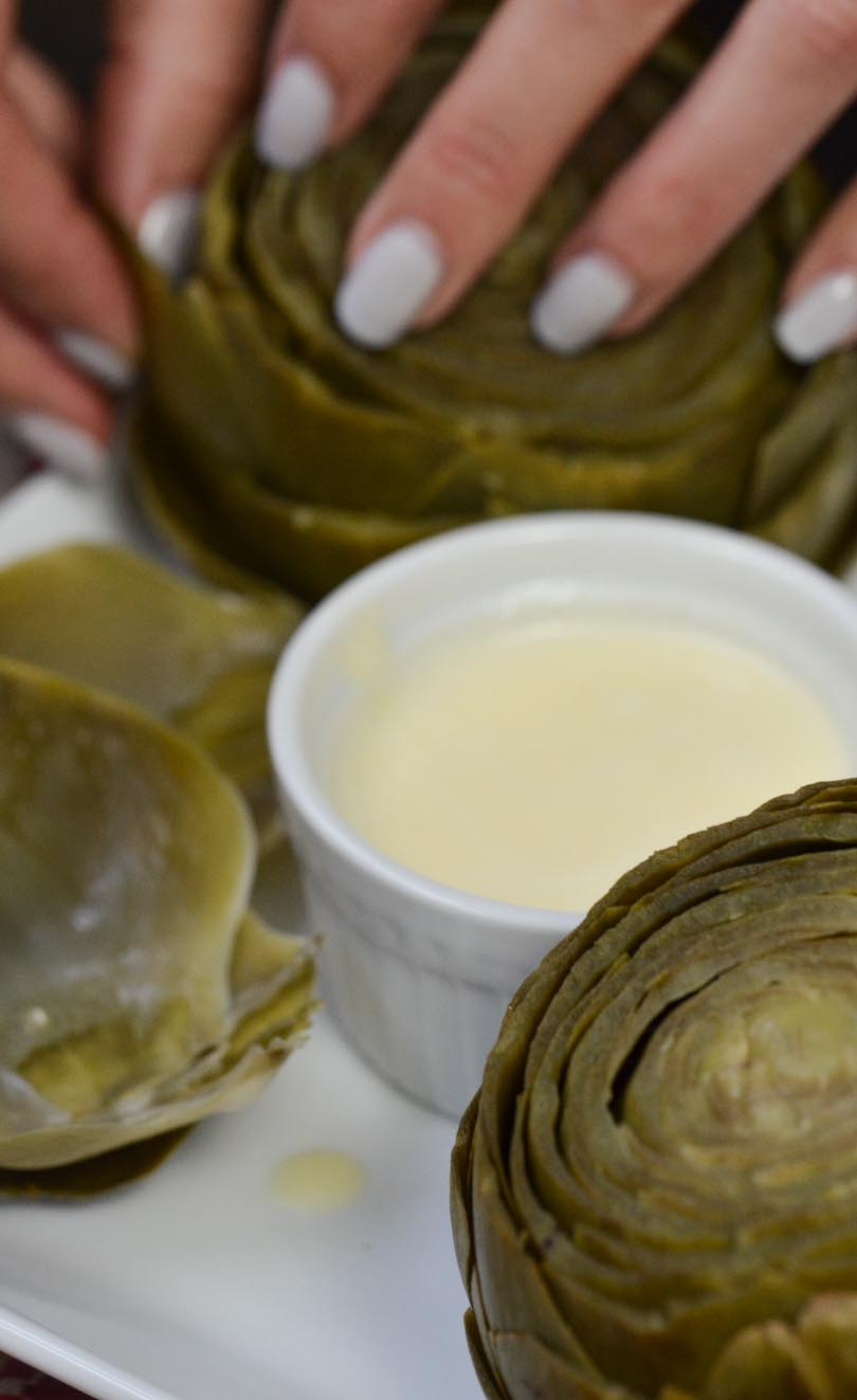 Artichoke with dish of vegan garlic butter dipping sauce made in our Vitamix.