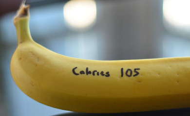 "A banana with ""Calories 105"" written on it in permanent marker."