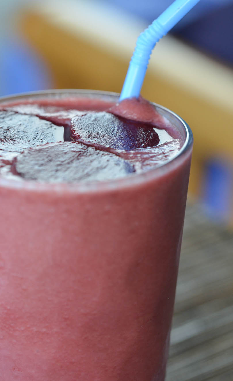 Bloody apple beet smoothie with a blue straw.