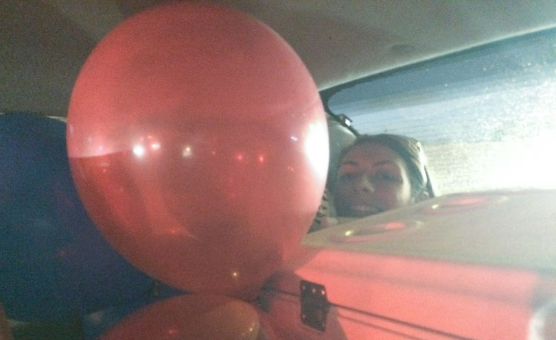 Red balloon and Shalva packed in car.