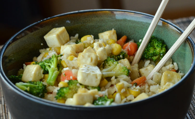 Cauliflower fried rice in bowl with chopsticks.