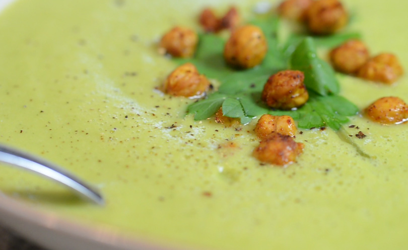 Super closeup of a zucchini coconut soup garnished with roasted chickpeas and parsley.