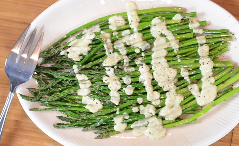 Vegan hollandaise sauce served over asparagus.