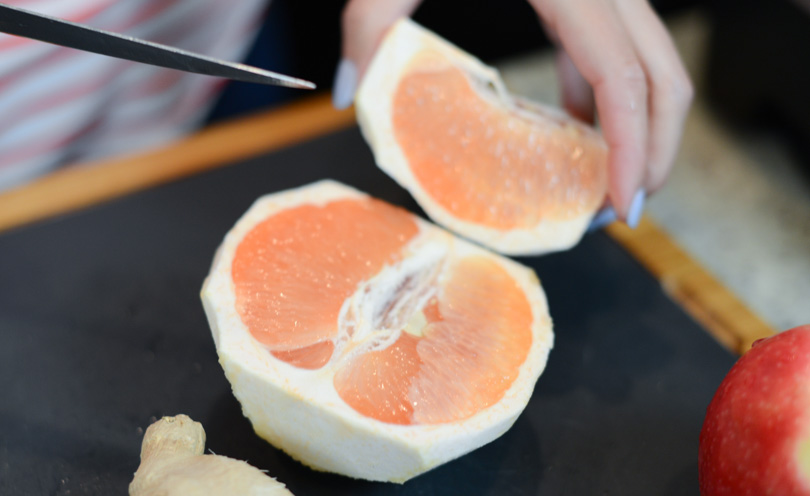 Slicing grapefruit for a grapefruit, ginger and apple for a smoothie called The Pinkman.