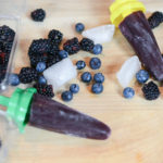 Three blueberry blackberry popsicles and their ingredients on cutting board.