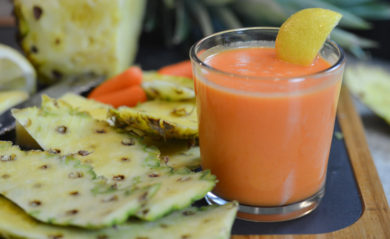 Invigorating pineapple-based, citrus carrot juice served with slice of lemon.