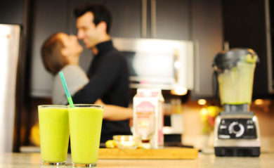 Lenny Gale and Shalva Geffen in the background of two green smoothies and a Vitamix Pro 750.