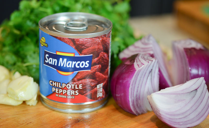 Can of San Marcos chipotle peppers next to red onion and cilantro.