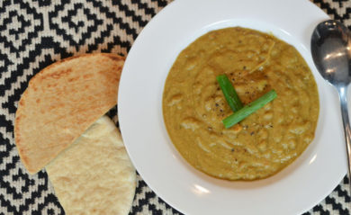 Lentil soup served in white bowl with pita bread.