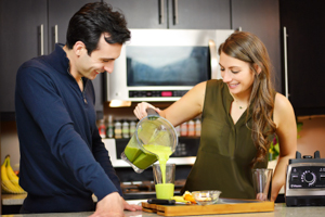 Lenny Gale and Shalva with a green smoothie and their Vitamix Pro 750.