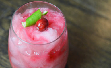 Merry mule, a frozen, pink beverage garnished with cranberry and lime garnish.