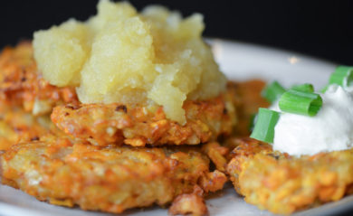 Sweet potato latkes with apple sauce on top and sour cream on side.