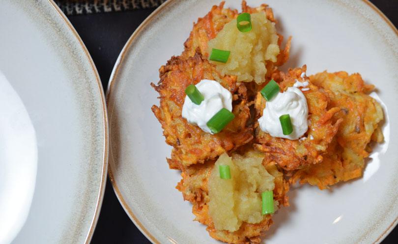 Sweet potato latkes with sour cream and apple sauce on top.
