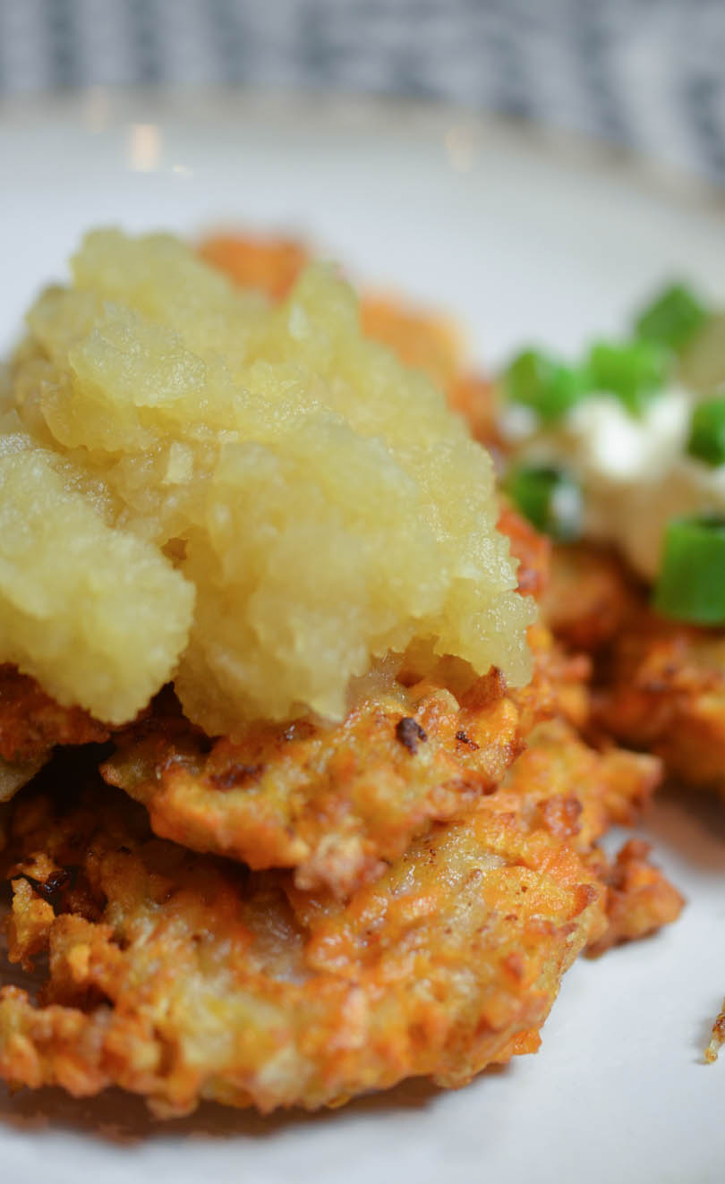 Sweet potato latkes with apple sauce on top and sour cream in background.