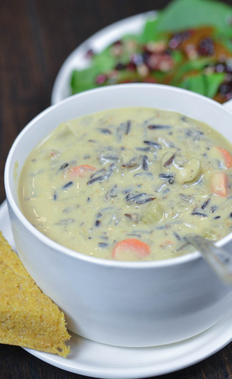 Vegan creamy wild rice soup steaming hot served with corn bread and salad.