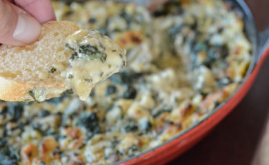 Dairy free artichoke dip on bread close up with full pan in background.