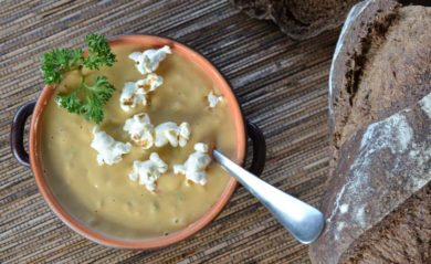 Vegan beer cheese soup with popcorn on top made in a Vitamix.