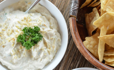 French onion dip served next to a bowl of salty tortilla chips.