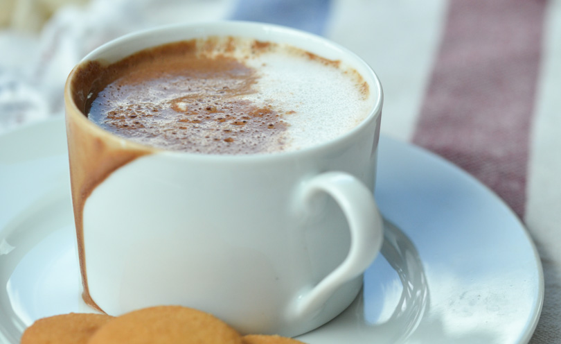 Mexican hot chocolate served in white mug with vanilla cookies.