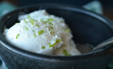 A scoop of coconut lime sorbet served in a black bowl.