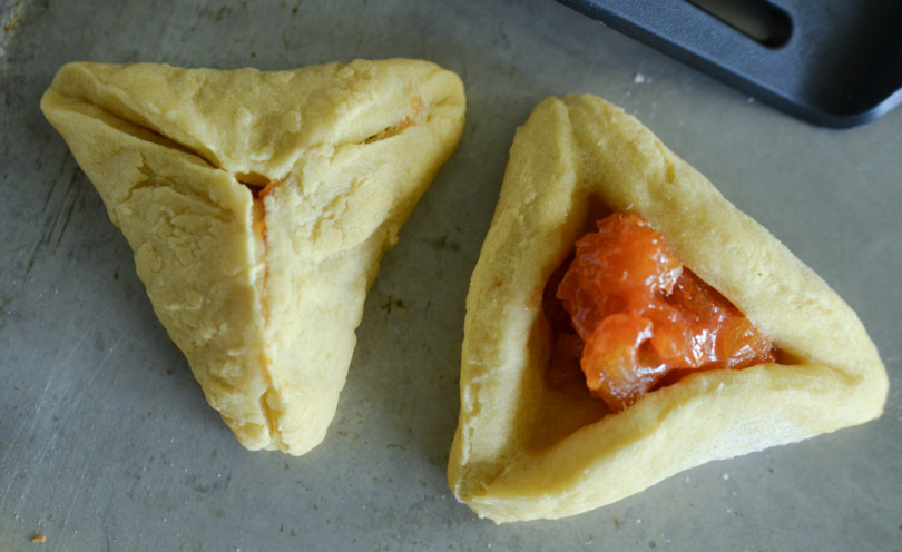 One open and one closed hamentashen with Vitamix in background.
