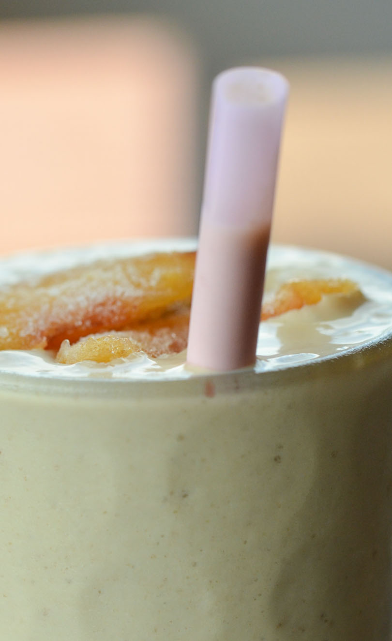 Peach pose smoothie from Life is NOYOKE served with a pink straw.