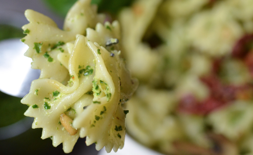 Fork full of bow tie pasta with pesto.