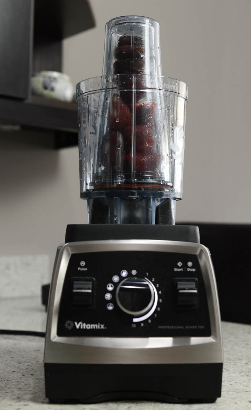 Vitamix 20 oz Personal Cup Adapter on a Pro 750 with strawberries and dates inside.