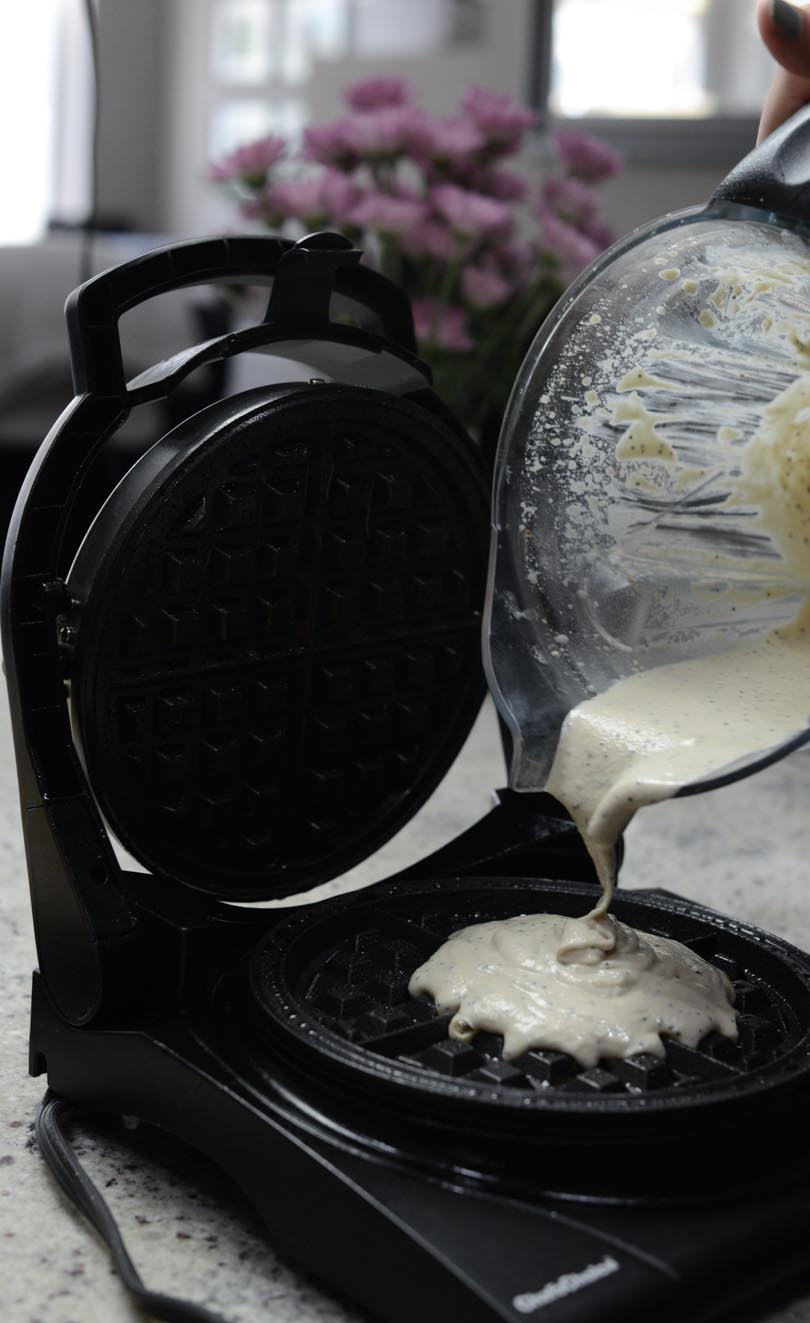 Pouring waffle batter from Vitamix container onto waffle iron.