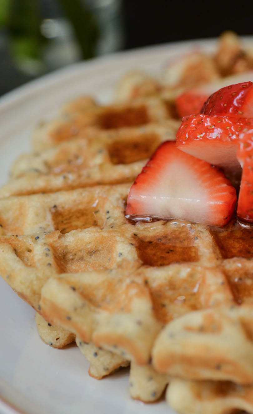 Close up of waffles with poppy seeds and lemon.