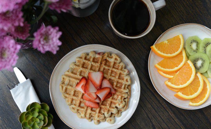 Waffles served for Mother's Day with flowers and coffee and fruit.