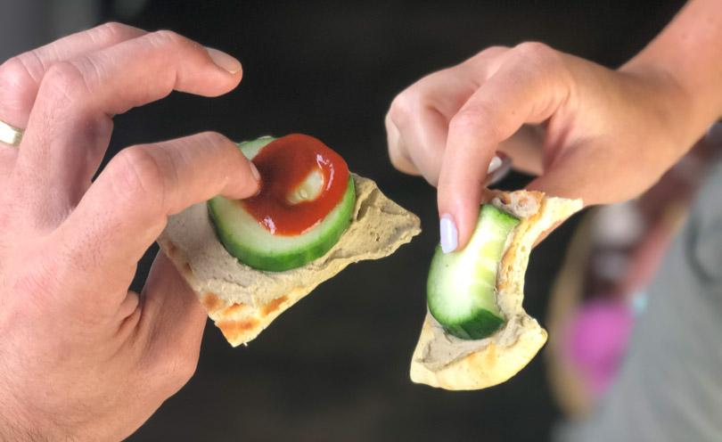 Shalva and Lenny holding hummus cucumber pita bites.