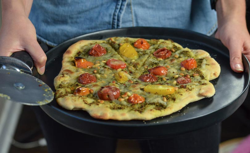 Serving pesto pizza on black plate.