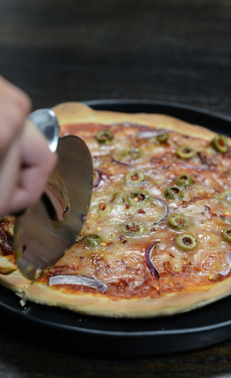 Slicing a pizza with crust made in a Vitamix.