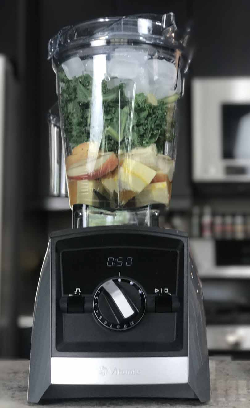 Vitamix A2500 with green smoothie ingredients inside.